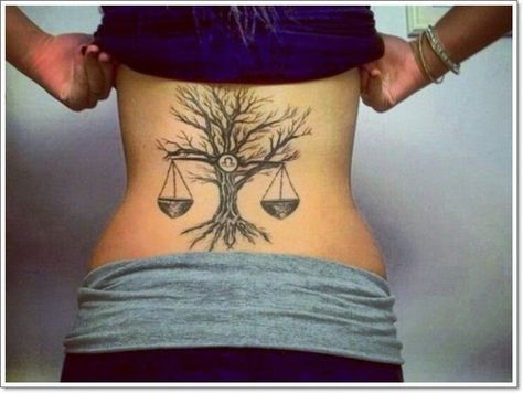 This is big Libra zodiac tat on back! In the middle there's tree with no leaves and quite big roots at the bottom. Libra is hanging on a tree trunk and you can see round libra zodiac sign in the middle of tree.