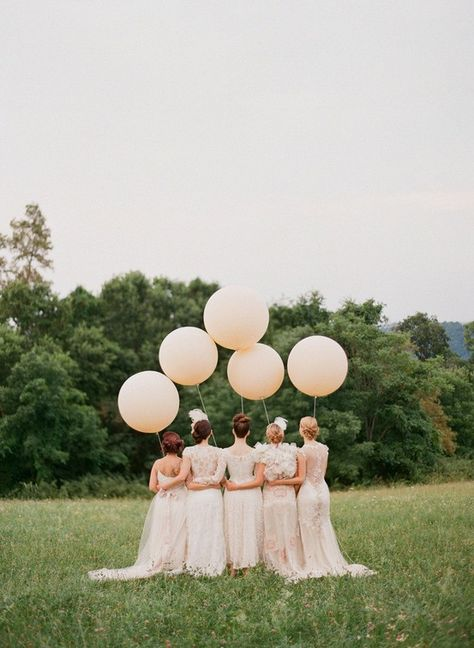 A gorgeous wedding photograph. Get the bride and bridesmaids all together and get them to turn away from the camera for once. It gives you chance to appreciate the dresses! The perfectly round balloons are a fun/quirky touch. Creative wedding photography like this is going to look wonderful for years.