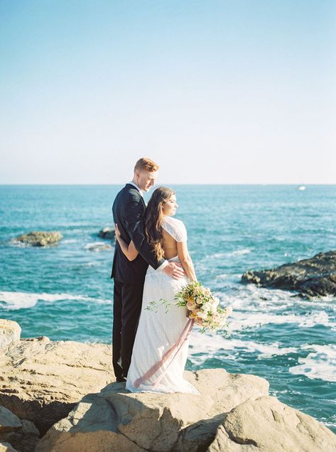 Southern California couple takes beautiful wedding portraits by the ocean in Dana Point, CA. Bride holding a lush, organic, summer bouquet made by San Diego floral designer, Le Champagne Projects. This garden style bouquet has beautiful garden roses, dahlias, and jasmine vine, wrapped in hand dyed velvet ribbon #fineartweddingflowers #fineartflowers #sandiegoweddingflorist #bridalbouquet #sandiegoflorist #summerbouquet #summerwedding #southerncaliforniaflorist