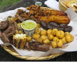 colombian BBQ style food, for picnics called fritanga colombiana: potatoes, plantains, corn, meats, avocado etc