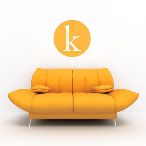 """Orange circular single letter wall sticker with the lowercase letter """"k"""" cut out. The decal is placed on a white wall above an orange modern couch."""