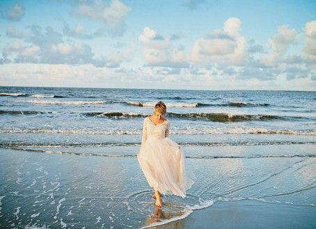 Stunning shot of bride walking on the shoreline | Captured by Amy Arrington Photography