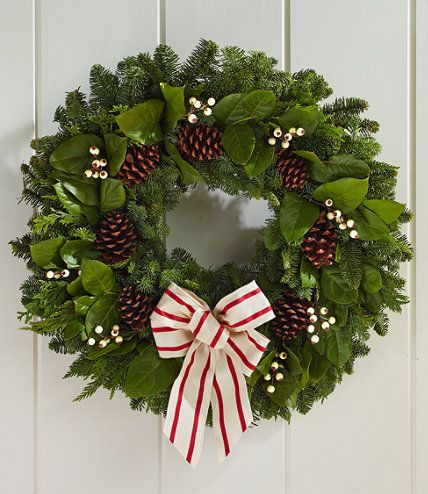 """Our Woodland Snowberry Wreath is the perfect way to welcome the season. Grown and made in the Pacific Northwest, our wreath features noble fir, western red cedar, broad-leaf salal and accented with natural pinecones and faux snowberries. Comes with a twill red and cream bow. 24"""" diameter. Wreath hanger is included. Made in the USA, decorations imported."""