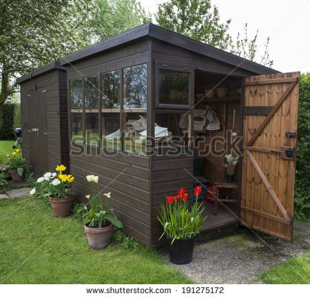 Garden Shed Exterior In Spring, With Shed Door Open, Lawn, Tools, Flowers