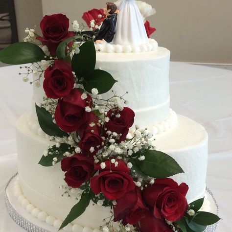 Two-tier oval wedding cake with red roses