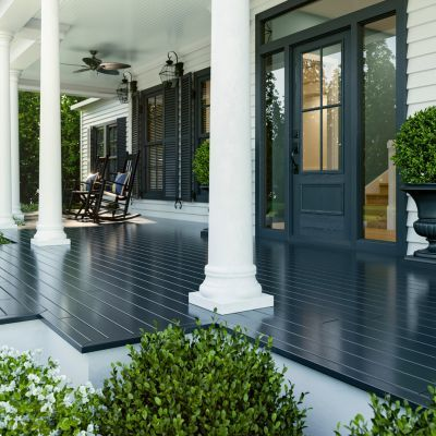 The Front Porch Of A Home With White Pillars Navy Floor And A Blue Front Door House With Porch Porch Colors Painted Front Porches