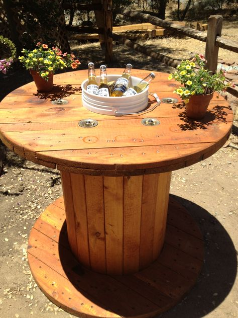 Love this idea. Wooden spool table.  Sanded and stained the spool.  Cut a hole in the middle and dropped in a 5-gallon paint bucket as a beer cooler!