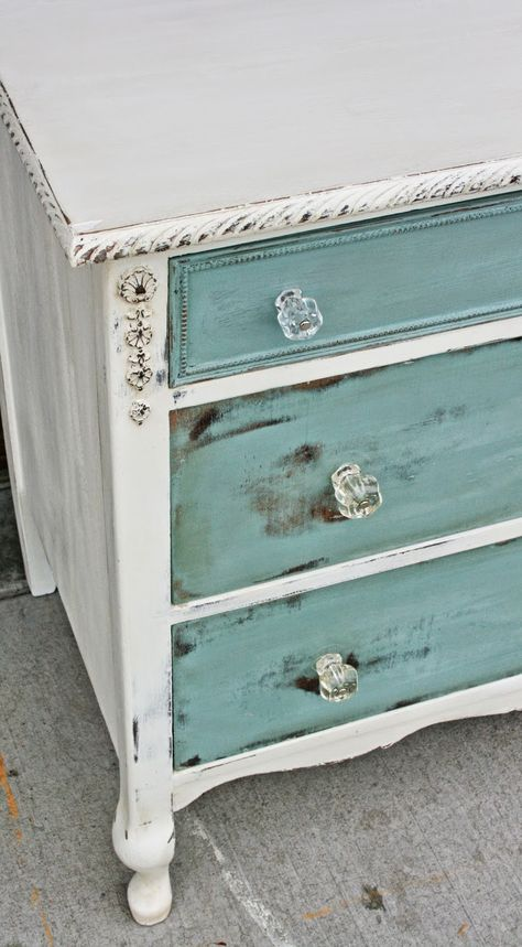 Antiqued white with sea blue drawers distressed. I love the glass knobs too