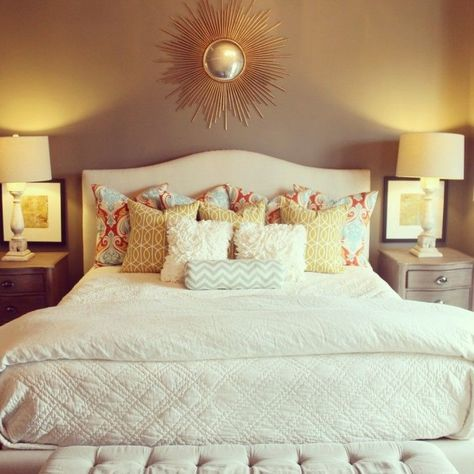 White bedding with colorful throw pillows.