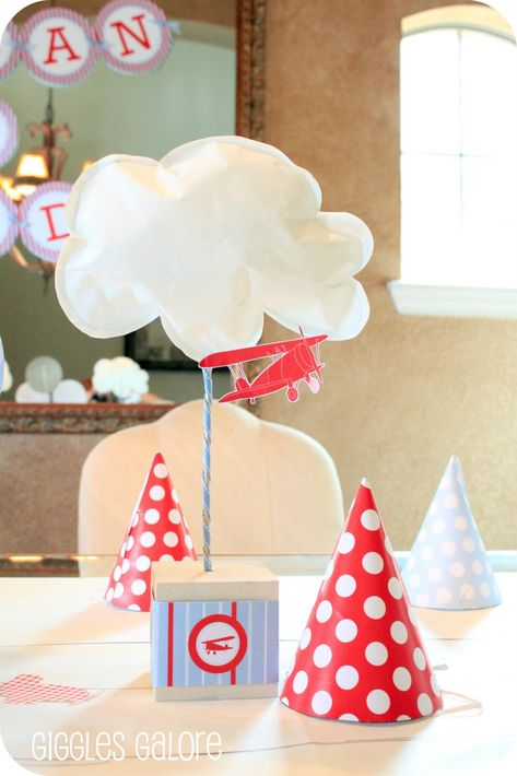 Centerpieces for airplane birthday party (Giggles Galore): Wrap a paper box in scrapbook paper, wrapping paper, or printable, and add an embellishment that's fitting with your theme