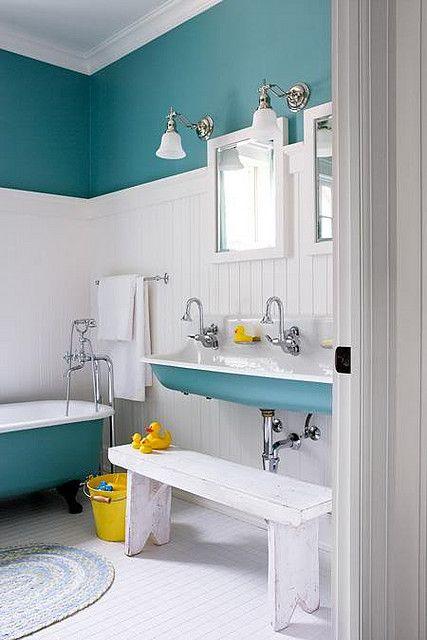 Salle de bain rétro en blanc et bleu vert. Le rappel du bleu sur la baignoire, le lavabo et le haut du mur fonctionne très bien.  Et avec en plus la touche de jaune, l'ensemble est vraiment frais et gai pour une salle de bain d'enfant par exemple.