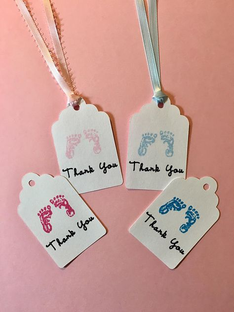 We have a set of 12 adorable hand stamped baby footprints baby shower tags. They are precious to use for an baby girl or baby boy baby shower. This thank you set of 12 baby shower favor tags are hand-stamped in pink, blue, brown or black ink. They can be a great addition to your