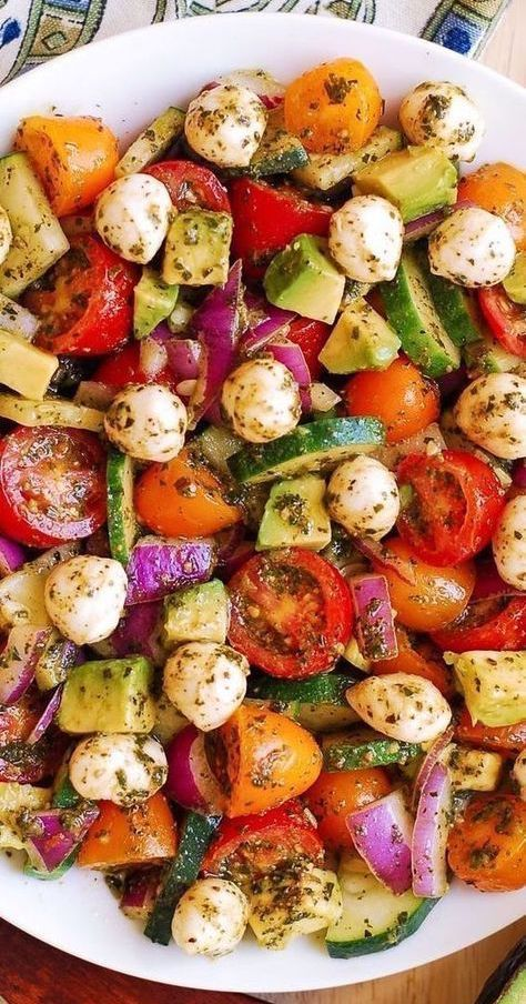 Tomato Cucumber Salad with Avocado, Mozzarella, and Basil Pesto. This healthy recipe is packed with nutrients and lots of fresh ingredients! Perfect Spring and Summer salad! Small fresh Mozzarella cheese balls are delicious when combined with avocado in this easy salad that also features red and yellow cherry tomatoes, cucumbers, and red onions. #easy #salad #easysalad #Spring #Summer #pestosalad #tomatosalad #cucumbersalad #tomatoes #cucumber #avocado #avocadosalad #healthysalad