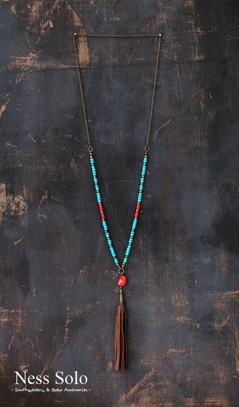 Sautoir sur une chaîne de laiton antique avec des perles de verre rouge bleu et lumineux, perles en métal, une perle de corail rouge et un gland en cuir