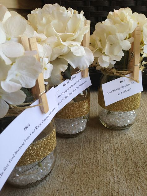 50th Birthday centerpieces, mason jars, twine, glitter, flowers. Use clothes pin to clip a featured event from their birth year.