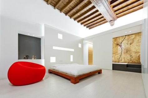 un plafond en bois à la française et un fauteuil rouge dans ...