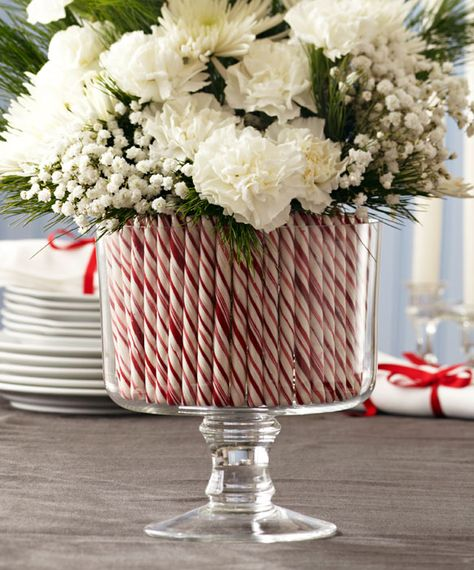 Fresh flowers in candy cane arrangement in clear glass trifle server.