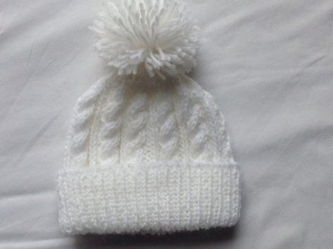 a9f4c41cb7e This warm and snuggly bobble hat has been hand knitted by me. It is a  traditional cable design in beautiful soft yarn. This hat is knitted from  Sirdar ...