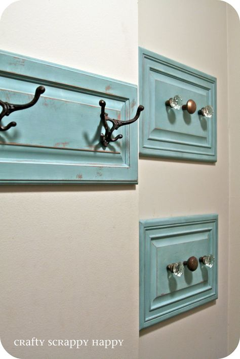 Coat hanger display from cabinet doors painted duck egg blue, distressed, and mounted with hooks or vintage door knobs.