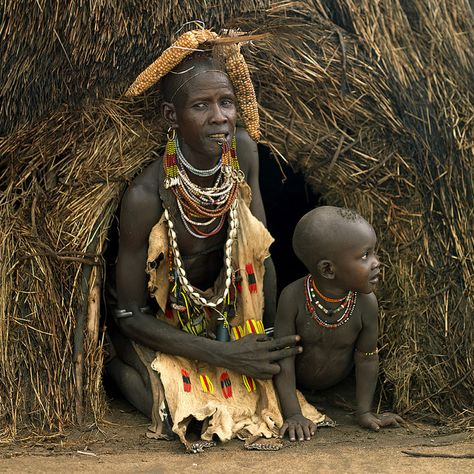 Karo tribe mother and chuld coming out from the house - Omo valley Ethiopia by Eric Lafforgue,
