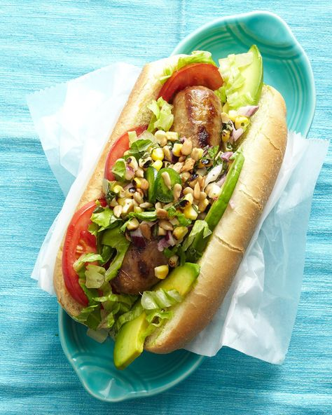 Quick-cooking and family-friendly, hot dogs are one of the best grilling recipes of all time. This recipe takes classic grilled frankfurters to a whole new level with lettuce, tomato, and avocado to complement the sausage sandwich. #grilling #summerrecipes #summergrilling #grillingrecipes #bestgrilledrecipes #bhg