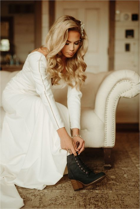 Stormi's wedding dress has us in love with the edgy, modern, chic, rock 'n' roll bridal style. This sleek white contemporary style wedding dress with long sleeves is to die for. Add in the unexpected buttons down the sleeve really add a pop of fabulousness that we can't describe. What also had us surprised were the black bridal boots that really popped up the edginess of her bridal look. Photography by TK Photography | The Magnolia Venue www.themagnoliavenue.com #smokymountainwedding