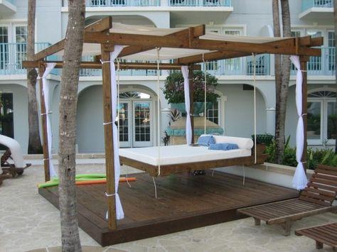 Hängebett mit Holzkonstruktion und weißen Vorhängen für Schatten - hangebett led beleuchtung