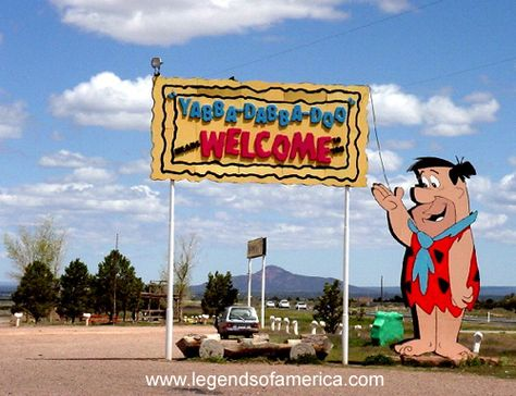 """(ARIZONA) Bedrock City at Valle, Arizona - Built in 1972 on the flat, arid plains south of the Grand Canyon, don't worry about the dinosaurs eating you here – heck, they don't even move. In the """"Theme Park,"""" you will find friendly and brightly painted statues of your favorite Flintstones characters, along with a man-made volcano, Flintstone mobiles, and brightly colored Bedrock buildings, including the homes of Fred and Barney's."""
