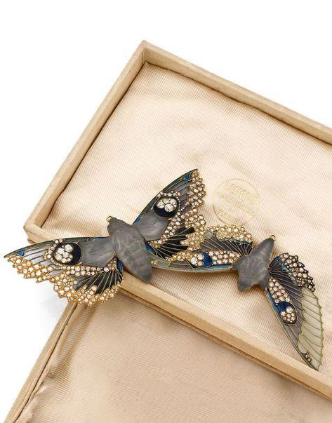 René Lalique, Rare et importante broche-pendentif devant de corsage en or jaune stylisée de deux papillons de nuit en vol, les corps en pâte de verre grise moulée au naturel, les ailes émaillées polychromes en pique-à-jour et serties de diamants taillées en rose et à l'ancienne. Photo Artcurial