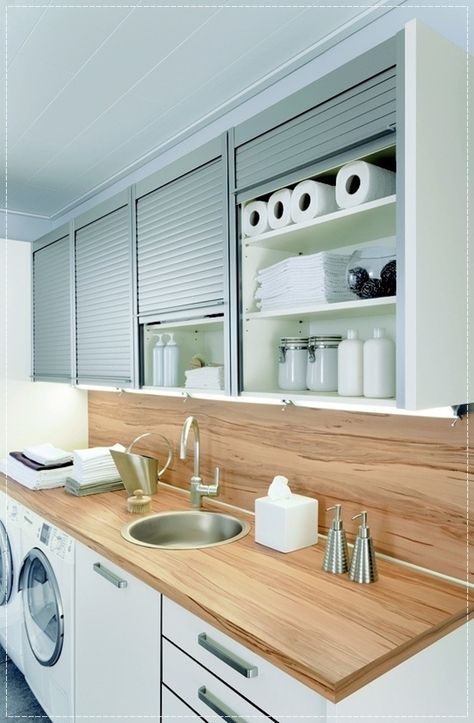 Like this idea for a laundry area; tucking under a workspace, sliding door utility cabinets