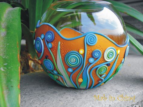 Polymer clay on vase with spirals.