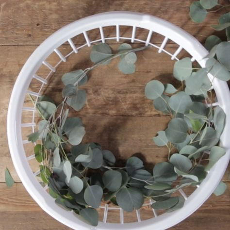 Hack alert! A plastic laundry basket results in a bold wreath of beautiful and trendy eucalyptus. It will make a beautiful base for holiday embellishments or a simple ornament for your front door all year long.