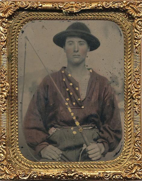 Teamster 1/9 plate ruby ambrotype in a  thermoplastic case presents a tinted young  rosy cheeked young man wearing a slouch hat  and bearing a whip.