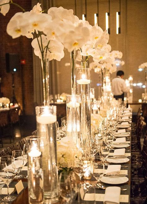 Tall glass vases are lush with white orchids and candles floating inside, complimenting this fabulous wedding table decor. #WeddingCenterpieces http://www.colincowieweddings.com/articles/real-weddings/modern-white-city-wedding
