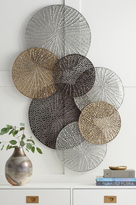 A stunning work that seems to float airily across your wall, the Adele Metal Wall Art is formed of laser-cut metal disks welded together forming a striking display. Each disk has a lacy, delicately textured cut-out design inspired by natural elements. The individual disk sections are finished in hues of silver, gold, and pewter, creating an on-trend contemporary sculptured look that's perfect for a modern transitional space.