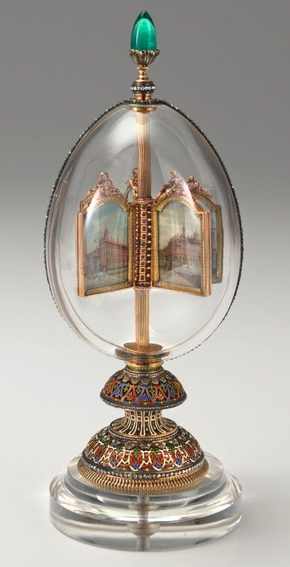 The Revolving Miniatures (Rock Crystal) Fabergé Egg: Presented by Nicholas to Alexandra in 1896. The outer shell is rock crystal. On the apex of the egg is a 27-carat Siberian emerald. The colorfully enameled base has the monograms of the Princess Alix of Hesse-Darmstadt (before her marriage) and later as Alexandra Feodorovna, Empress of Russia. Each monogram is surmounted with a diamond crown of the respective royal house and these monograms form a continuous pattern around the base of the…