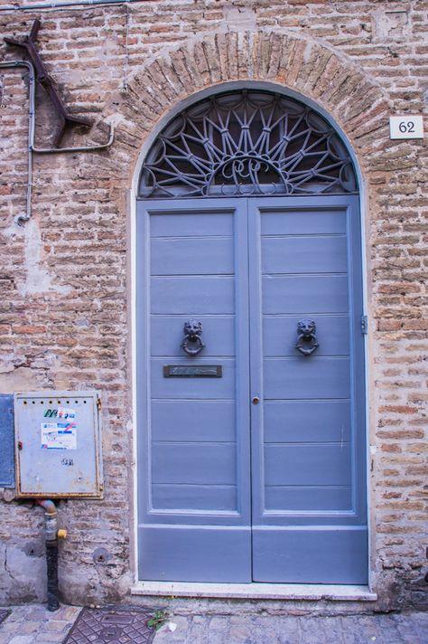 Grey door with double lion head door knockers in Senigallia, Marche Region, Italy