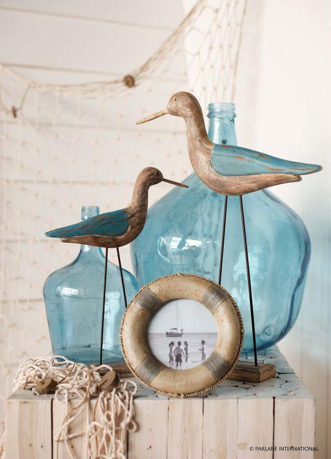 Blue glass bottles and nautical frames create a seaside theme