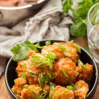 Crispy panko-coated cauliflower florets are baked up and drenched in spicy gravy in this lightened-up take on cauliflower Manchurian. A healthy vegan version of a Chinese-Indian classic! #veganrecipes #indianrecipes #chineserecipes #cauliflower