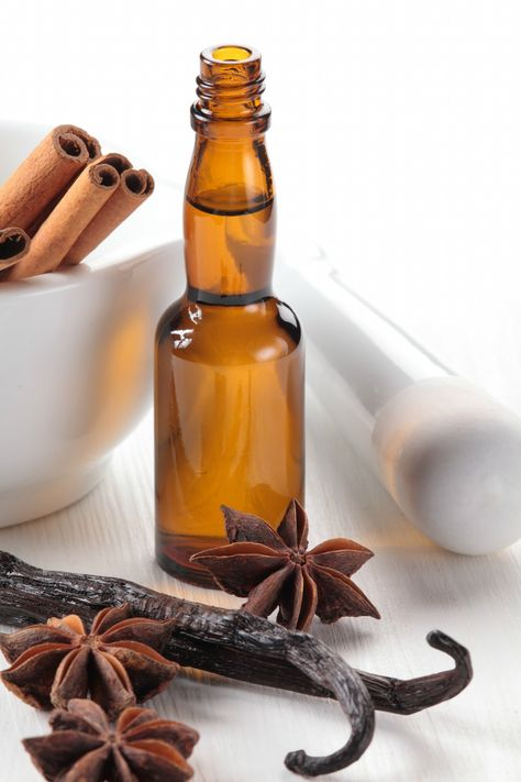 Close-up of vanilla beans, anise stars, mortar and baking flavor in a bottle
