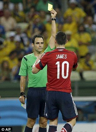 Referee Carlos Velasco Carballo from Spain shows a yellow card to Colombia's James Rodrigu...
