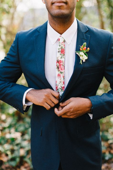 a navy suit, a white shirt plus a pink florla print tie for a bright and cheerful summer wedding look