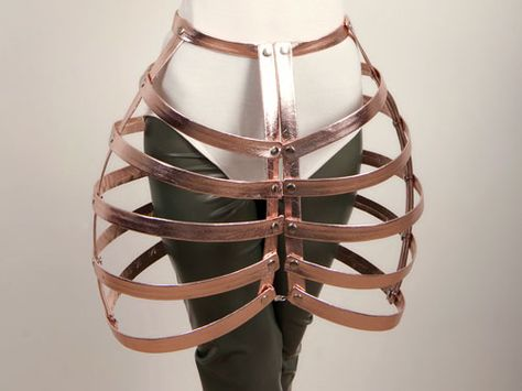 A boning outerwear structure covered in leather and held in place by nickel rivets. Cage has hooks and eyes down front and back to fasten.