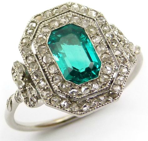 Antique Belle Époque emerald and diamond cluster ring with a trap-cut emerald is set within two rows of millegrain-set rose diamonds. Outside of the double halo, the ring has bow-shaped, diamond-set shoulders. Via Diamonds in the Library.