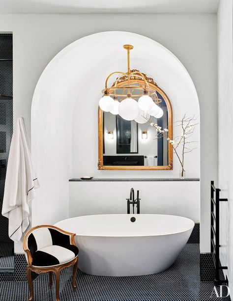 A Ralph Lauren Home light fixture illuminates a Victoria + Albert tub in the master bath of Naomi Watts and Liev Shreiber's New York City apartment, which was designed by Ashe + Leandro. See more luxurious celebrity bathrooms now.