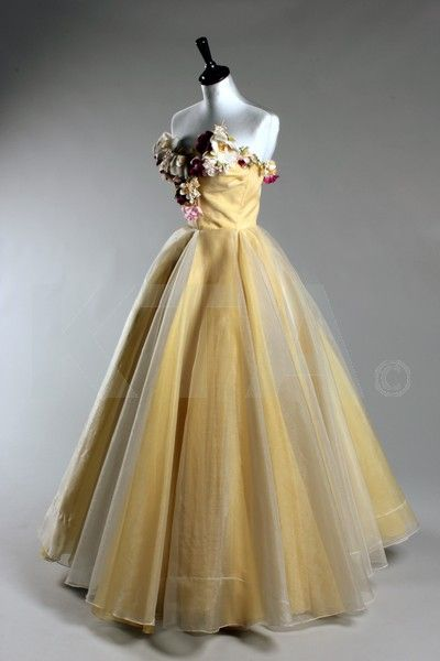 A romantic Madame Grès ball gown which also produced dresses in the mid 1950s. The top part is adorned with garlands of silk flowers and the dress formed from white and yellow chiffon, organza and taffeta. It also has a layer of glistening white horsehair which adds to its delicate and feminine vibe. www.vintageclothin.com