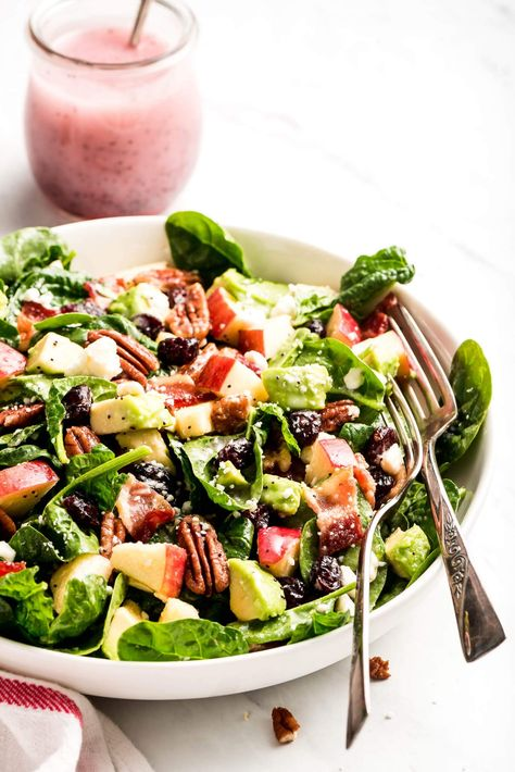 Apple & Bacon Spinach Salad is the perfect side salad for fall. The combination of salty bacon, pecans, creamy avocado, and sweet apples and dried cranberries, all tossed in a homemade poppy seed dressing is amazing! #spinachsalad #sidesalad #bacon   GarnishandGlaze.com