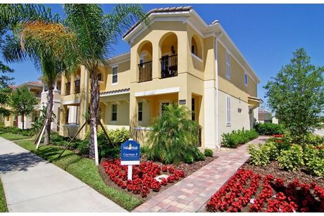 Bright red flowers pop against pale yellow walls. The Cayman II plan. Newly built townhomes by DiVosta Homes. The VillageWalk at Lake Nona community in Orlando, FL.