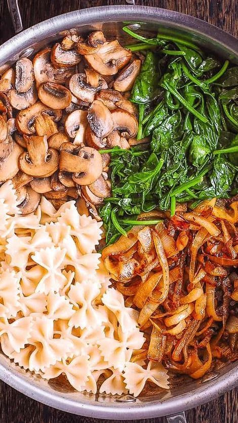 Creamy Bow-Tie Pasta with Spinach, Mushrooms, and Caramelized Onions. This simple meatless Italian dinner is pure comfort food! The bow-tie shaped pasta is perfectly matched with rich and buttery Parmesan sauce! #bowtiepasta #creamypasta #meatlesspasta #meatless #pastadinner #bestpasta #Italianpasta #farfalle #pastarecipe #mushroompasta #spinachpasta #caramelizedonions