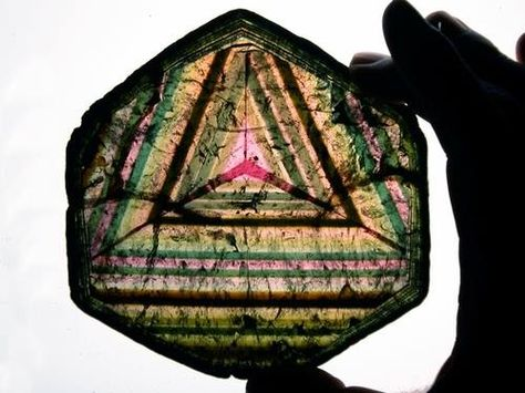 Rare Cross Section of Tourmaline  Polished slice of a transparent tourmaline crystal showing colorful internal zoning. The most amazing fact of this piece is the triangular pattern that appear throughout the section. Perfectly formed geometric shapes like this, naturally occurring in a mineral's formation, are rare.